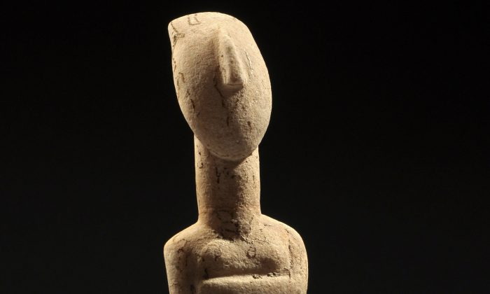 A detail from an elegant stylized nude figure of the early Spedos type, her arms are folded beneath her breasts, her slender lyre-shaped head with wedge-shaped nose and long oval neck; incised details, with traces of red pigment and strong root marks. Early Bronze Age II, ca. 2600-2500 BC. H. 9 11/16 in. (24.6 cm.)   (Royal-Athena Galleries)