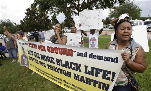 Demonstrators hold banners and signs and shout outside the Seminole County Courthouse, while the jury deliberates in the trial of George Zimmerman, Friday, July 12, 2013, in Sanford, Fla. Zimmerman has been charged with second-degree murder for the 2012 shooting death of Trayvon Martin. (AP Photo/John Raoux)