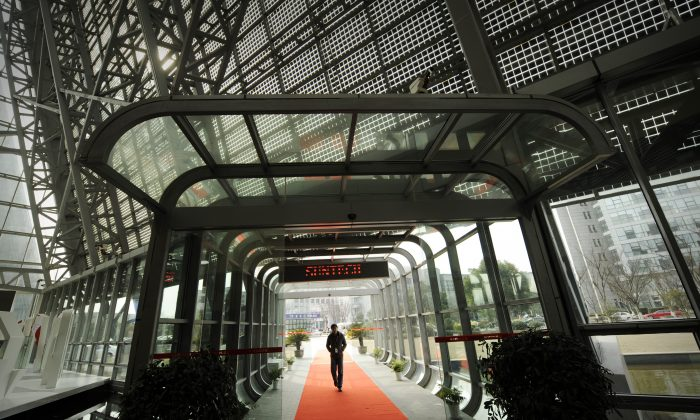 A visitor enters the offices of the now bankrupt Chinese company Suntech in the eastern Chinese city of Wuxi, Feb. 27, 2012. One of its subsidiaries filed for bankruptcy earlier this year, highlighting the perils now facing many industries that accumulated overcapacity over years of artificially cheap financing. (Peter Parks/AFP/Getty Images)