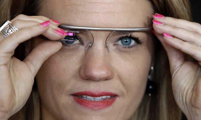 """FILE - In this Wednesday, May 29, 2013 file photo, Sarah Hill, a Google Glass contest winner, of Columbia, Mo., tries out the device, in New York. """"This is like having the Internet in your eye socket,"""" Hill said. """"But it's less intrusive than I thought it would be. I can totally see how this would still let you still be in the moment with the people around you."""" (AP Photo/Frank Franklin II, File)"""