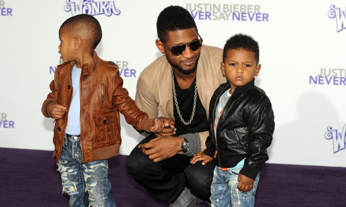 """Singer Usher arrives with his children at the premiere of """"Justin Bieber: Never say Never"""" in Los Angeles, California on February 8, 2011. (GABRIEL BOUYS/AFP/Getty Images)"""