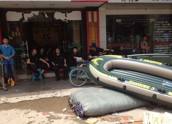 A rescue team is seen sitting in the shade beside a rescue boat in Chendian Town in Shantou City in Guangdong Province, while victims stranded by the flood are waiting for help. Netizens have reported the rescue teams would only act if residents first paid them. (Weibo.com)