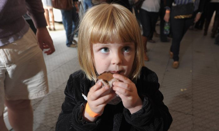 A young girl indulges in a bite to eat during an even in New York in this file photo. Recent studies show that involving your child in the cooking process and having it eat a lot of raw produce will benefit it over the long term. ((Michael Loccisano/Getty Images for City Harvest)