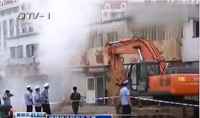 A scene from the demolition, where Wang throws crackers onto the bulldozers and 'chengguan' who had come to evict him. (Weibo.com)
