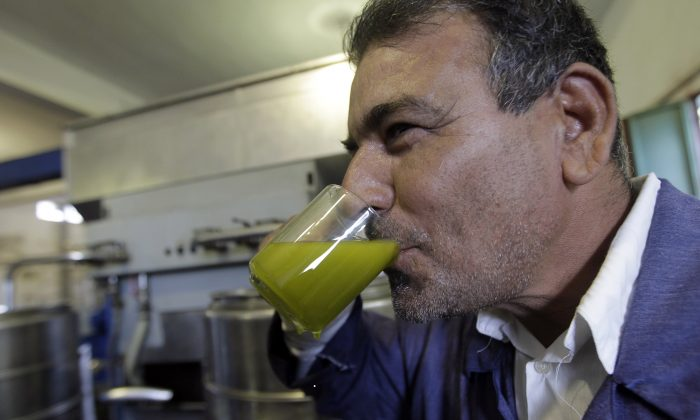 A Libyan man tastes freshly pressed olive oil to check the quality at an olive press in the town of Zliten, east of the capital Tripoli, on Nov. 11, 2011. (Joseph Eid/AFP/Getty Images)