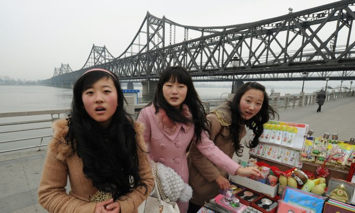 Chinese tourists buy North Korean souvenirs beside the Yalu River Bridge leading to North Korea at the Chinese border town of Dandong on December 28, 2011. (Mark Ralston/AFP/Getty Images)