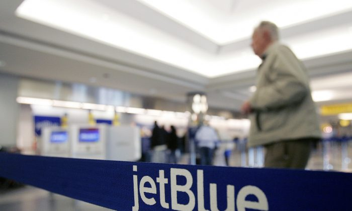 In this Wednesday Feb. 1, 2006, file photo, a pedestrian makes his way to the e-ticket counter of JetBlue at New York's LaGuardia Airport. (AP Photo/Frank Franklin II, File)
