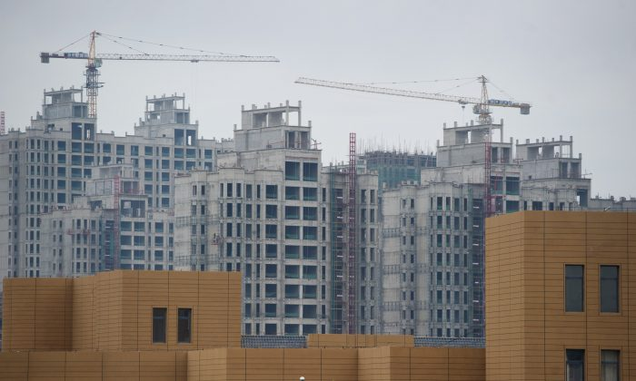 """A photo taken on Aug. 18, 2012 shows ongoing construction in the inner Mongolian city of Erdos, in spite of the difficulty the city has had filling office and apartment buildings already built. Recent financial difficulties have caused Erdos, formerly known as a """"ghost city"""" to become known as a """"debt city."""" (Ed Jones/AFP/GettyImages)"""