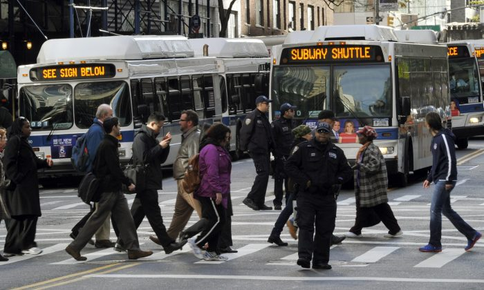 A traffic officer directs people to MTA buses used for subway shuttles on 57th street on November 1, 2012 in New York City. (TIMOTHY A. CLARY/AFP/Getty Images)