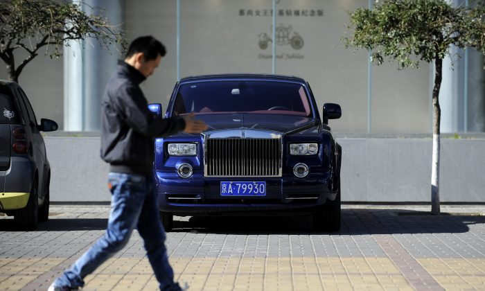 This picture taken on Oct. 31, 2012, a Chinese man walks past a Rolls-Royce outside an auto shop in Beijing. Only a quarter of wealthy Chinese are very confident in the Chinese economy. (Wang Zhao/AFP/Getty Images)