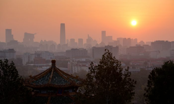 The sun rises above the Beijing skyline early on Nov. 6, 2012. The Chinese Communist Party will collapse in three stages in the next three years and its reign will come to an end by 2016, according to the Hong Kong magazine Frontline. (Ed Jones/AFP/Getty Images)