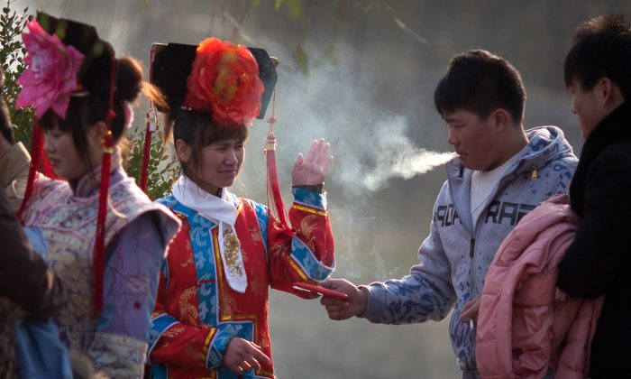 A tourist dressed in Qing dynasty style clothing waves away cigarette smoke in Beihai park in Beijing on Dec. 4, 2012. Efforts to curb smoking in China have not been much of a success owing to widespread ignorance of the laws and lack of enforcement. (Ed Jones/AFP/Getty Images)