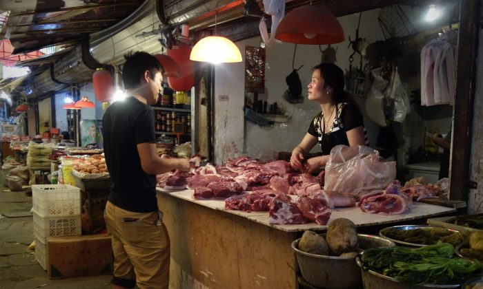 In this picture taken on June 1, 2013 a man (R) browses meat at a shop selling pork in Beijing. An abattoir in Beijing was recently found to have been selling diseased meet to high schools for over a year. (Wang Zhao/AFP/Getty Images)