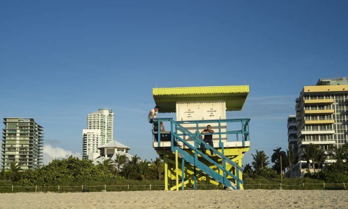 People sit in a lifeguard's tower on the beach on June 9, 2013 in Miami Beach. (BRENDAN SMIALOWSKI/AFP/Getty Images)