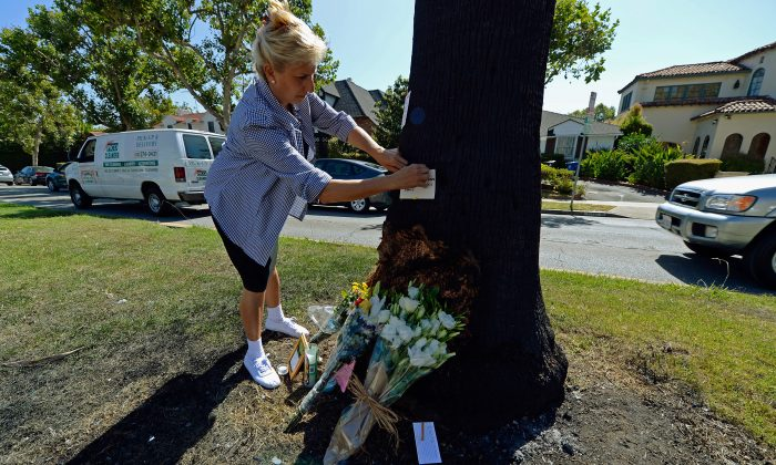 Ann Adams, who lives across the street, pins a condolence note to a makeshift memorial at the crash site of award-winning journalist Michael Hastings on June 19, 2013 in Los Angeles, California. Hastings, 33, whose reporting for Rolling Stone helped bring down Stanley McChrystal, the top U.S. general in Afghanistan, died on June 18 when his car crashed into a tree and caught fire. (Kevork Djansezian/Getty Images)