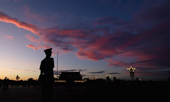 """A Chinese paramilitary policeman guards at Tiananmen Square under crimson clouds at sunset after several days of heavy air pollution on July 4, 2013 in Beijing, China. An August 5, 2013 editorial from the Global Times, a state-run news agency, says that the Chinese Communist Party's collapse will only bring """"battles and bloodshed,"""" a claim highly disputed by Chinese netizens. (Feng Li/Getty Images)"""