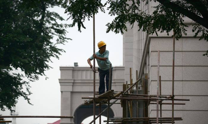 This picture taken on July 11, 2013 shows a Chinese worker putting up the scaffolding at a construction site in Beijing. The Chinese economy could be $1 trillion smaller than thought, according to an economist's number crunching. (WANG ZHAO/AFP/Getty Images)