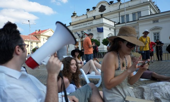 A man shouts slogans in a megaphone as protesters wearing swim suits attend a beach-party-style anti-government demonstration in front of parliament buildings in central Sofia, Bulgaria, on July 31, 2013. Bulgarians have been taking to the streets in the thousands across the country since June 14, calling for the resignation of what they call a mafia-influenced government. (Dimitar Dilkoff/AFP/Getty Images)