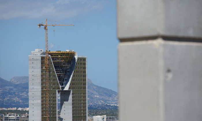 """A crane  stands on top of In Tempo building on August 9, 2013 in Benidorm, Spain. The construction of the In Tempo building began during the economic boom and was meant open in 2009 as the tallest residential building  within the E.U. at almost 200 metres high. However after a catalogue of building problems the 47-story twin tower building remains unfinished and has been transferred to the SAREB or """"Bad Bank.""""  (Photo by Pablo Blazquez Dominguez/Getty Images)"""