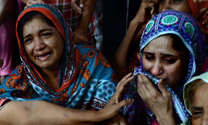 Pakistani women mourn the death of a relative who was killed after drinking toxic liquor in Karachi on Aug. 11, 2013. (Rizwan Tabassum/AFP/Getty Images)