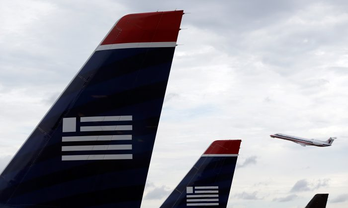 An American Airlines jet takes off behind US Airways jets at Ronald Reagan Washington National Airport in Arlington, Va., Aug. 13, 2013. The Department of Justice filed an antitrust lawsuit Tuesday to block the planned merger of US Airways and American Airlines. (Win McNamee/Getty Images)