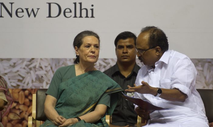 Sonia Gandhi (L) listens to Indian Food Minister K.V. Thomas (R) during the launch of the Food Security Programme in New Delhi on August 20, 2013.  (RAVEENDRAN/AFP/Getty Images)
