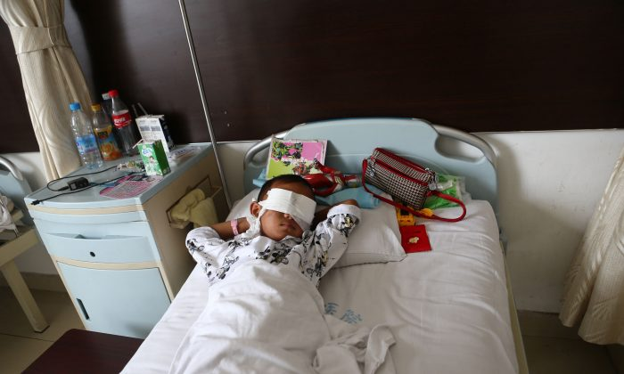 A young boy recovers in hospital in northeast China on Aug. 27, after his eyes were gouged out by a woman who may have been an organ trafficker. (STR/AFP/Getty Images)