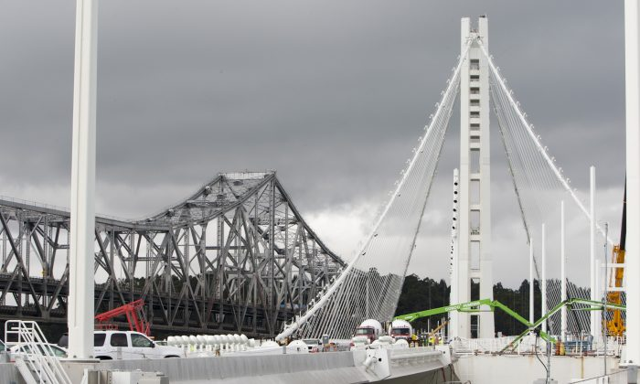 The new eastern span of the San Francisco–Oakland Bay Bridge under construction, with the old span in the background (L) in Oakland, Calif., Aug. 8, 2013. (Alex Ma/Epoch Times)