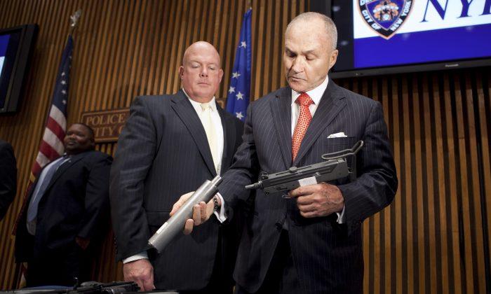 Commissioner Ray Kelly (R) looks at a Mac 10 gun with a flash suppressor. (Samira Bouaou/Epoch Times)