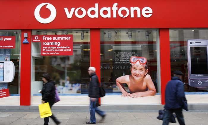 People walk by a branch of Vodafone in central London is seen in a 2009 file photo. Britain's Vodafone PLC, one of the world's largest mobile phone companies, confirmed that it was in discussions with Verizon Communications to sell its 45 percent stake in the Verizon Wireless (AP Photo/Sang Tan, File)