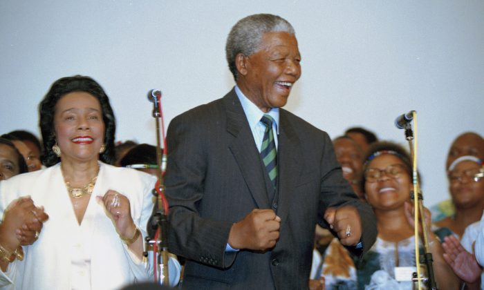 In this May 2, 1994 file photo Nelson Mandela, and Coretta Scott King, left, widow of slain civil rights leader Martin Luther King, Jr., sing and dance at a victory celebration for Mandela in Johannesburg, after Mandela and the ANC appeared to take the majority of the votes in the country's first integrated elections. (AP Photo/David Brauchli,file)