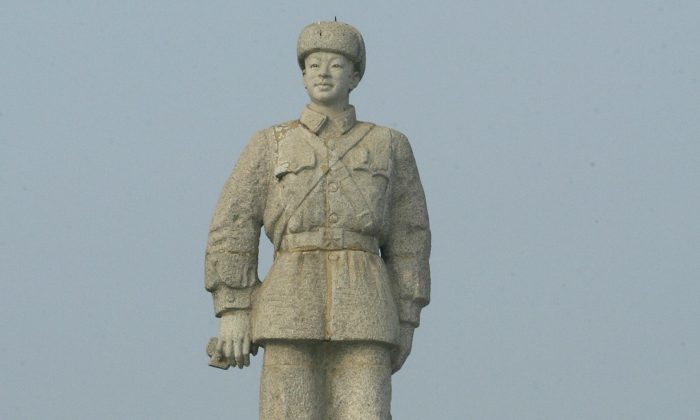Students linger beneath a statue of Lei Feng, one of the heroes of China's ruling Communist Party, Oct. 28, 2004. Two men were arrested recently after being accused of defaming the communist idol. (Frederic J. Brown/AFP/Getty Images)
