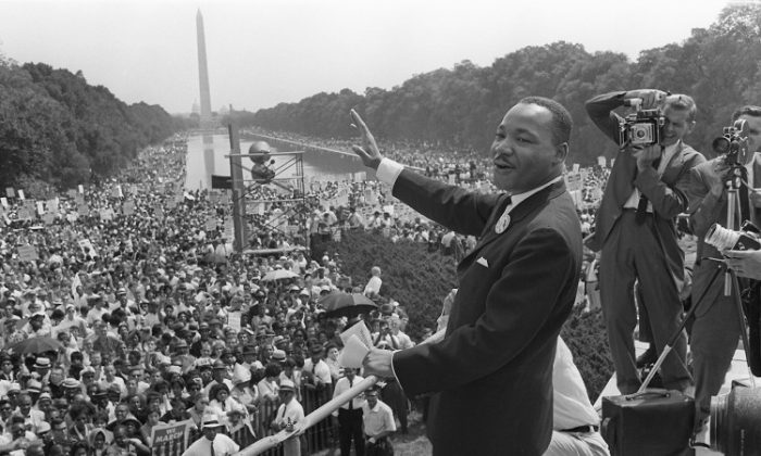 """The civil rights leader Martin Luther KIng (C) waves to supporters August 28, 1963, on the Mall in Washington, D.C. during the """"March on Washington."""" (AFP/Getty Images)"""