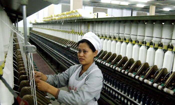 This file photo dated 30 March 2004 shows a Chinese worker going about her chores at a factory manufacturing textiles for export in Haikou, on the southern Chinese island of Hainan. Current data and anecdotes indicate that foreign manufacturers are seeking cheaper places of production than China. (AFP/AFP/Getty Images)