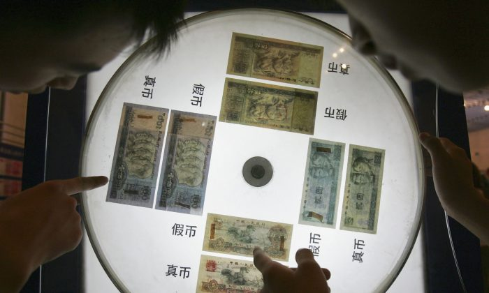 A show window displaying yuan notes and showing how to identify real and fake notes at an exhibition of the Chinese currency Yuan at the Beijing Science Museum on July 22, 2005 in Beijing, China. Debt is being accumulated in China in the pursuit of economic growth. (China Photos/Getty Images)