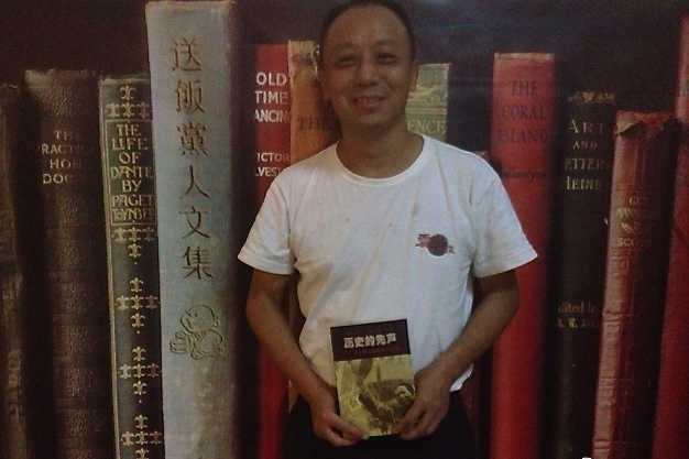 """A photo of Xiao Shu, 51, dated May 13, 2013, holding up a book titled """"History's Herald"""" at a Chinese event. Xiao, a prominent veteran journalist, was detained on Friday after he called for the release of a fellow human rights activist, Xu Zhiyong, jailed on July 16. (Sina Weibo)"""