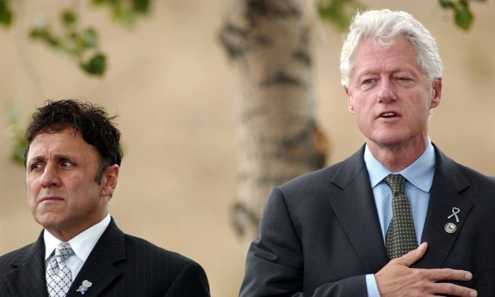 Columbine Principal Frank DeAngelis (L) and Former U.S. President Bill Clinton sing the Star Spangled Banner at a groundbreaking ceremony in Clement Park not far from Columbine High School in Littleton, Col., on June 16, 2006. (Thomas Cooper/Getty Images)