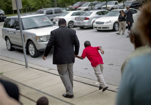 Ronald E. McNair Discovery Learning Academy teacher Brandon Graham walks a student to a car as he is picked up by a loved one at the end of their first day of classes at McNair High School Wednesday, Aug. 21, 2013 after a man with an assault rifle and other weapons entered the academy Tuesday and shot at police from inside, in Decatur, Ga. (AP Photo/David Goldman)