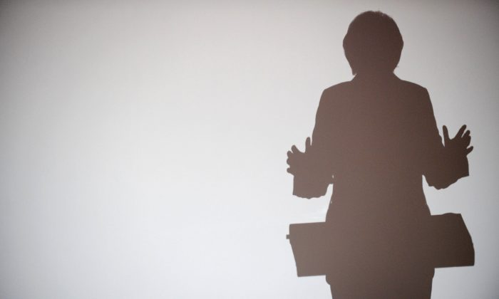 In this March 2009 file photo, German Chancellor Angela Merkel casts her shadow on the wall as she delivers a speech in front of the federal Association of German Banks in Berlin. The so-called shadow banking market is comprised of unregulated nonbank financial intermediaries, such as hedge funds. (Steffi Loos/AFP/Getty Images)