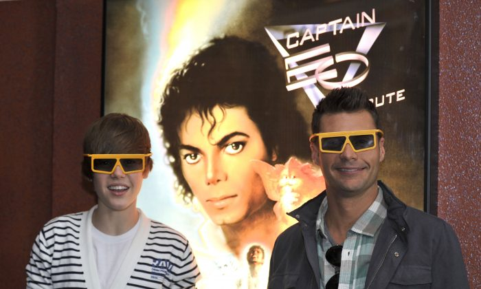 In this handout image provided by Disneyland, Ryan Seacrest (R) and Justin Bieber prepare to watch 'Captain EO' with more than 500 fans at Disneyland on March 26, 2010 in Anaheim, California. A picture of deceased pop star Michael Jackson is in the background. (Lisa Rose/DisneyLand via Getty Images)