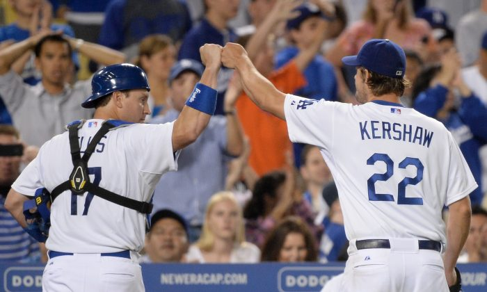 Clayton Kershaw (R) of the Los Angeles Dodgers celebrates the third out of the eighth inning with A.J. Ellis against the Cincinnati Reds at Dodger Stadium on July 26, in Los Angeles, Calif. (Harry How/Getty Images)