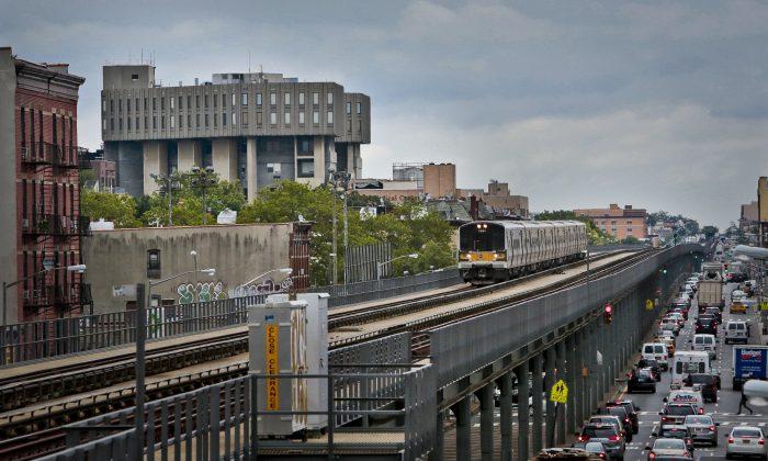 A LIRR train travels past the Interfaith Medical Center, left, in New York on Thursday, July 25, 2013. (AP Photo/Bebeto Matthews)