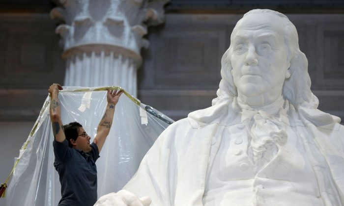 A workman wraps a statue of Benjamin Franklin in aprotective cover in preparation for upcoming construction at the The Franklin Institute in Philadelphia on Aug. 20, 2013. (AP Photo/Matt Rourke)