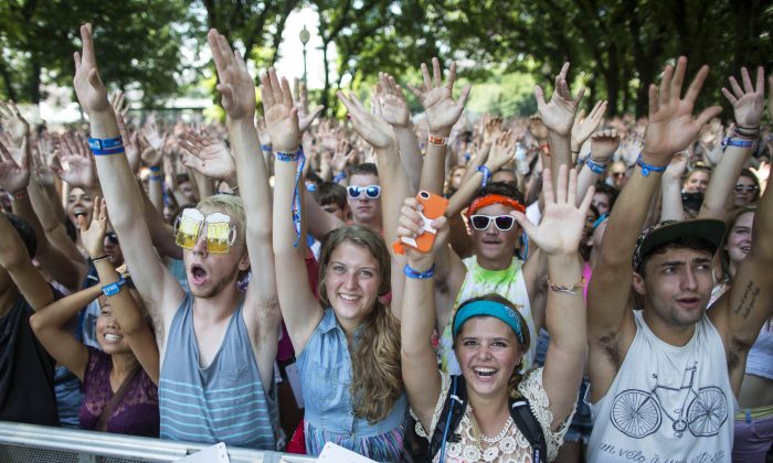 Fans raise their hands during a performance by rock band American Authors at the Lollapalooza Festival in Chicago, Friday, Aug. 2, 2013. The festival, which opened Friday, continues through Sunday in Chicago's lakefront Grant Park. (AP Photo/Scott Eisen)