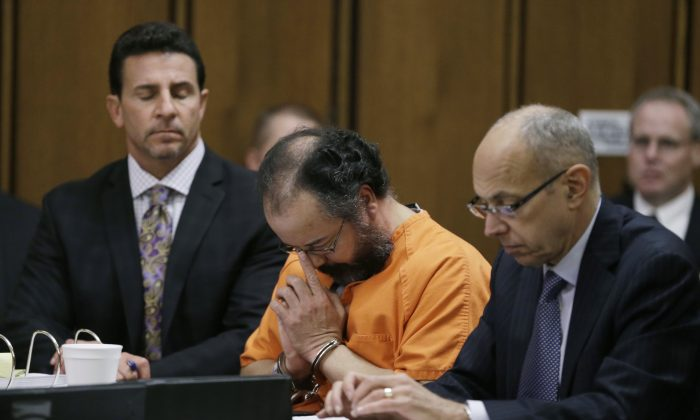 Ariel Castro, center, adjusts his glasses during the sentencing phase Thursday, Aug. 1, 2013, in Cleveland. Defense attorney's Craig Weintraub, left, and Jaye Schlachet listen. Castro, convicted of holding three women captive in a house he turned into a prison and raping them repeatedly for a decade, was sentenced Thursday to life without parole plus 1,000 years. (AP Photo/Tony Dejak)