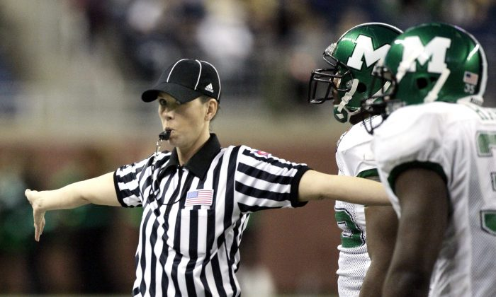 In this Dec. 26, 2009, file photo, line judge Sarah Thomas blows her whistle to stop the clock during the Little Caesars Pizza Bowl NCAA college football game between Marshall and Ohio in Detroit. Thomas is on track to become the NFL's first permanent female official, possibly as early as 2014, and is a finalist in the NFL's scouting program. (AP Photo/Duane Burleson, File)