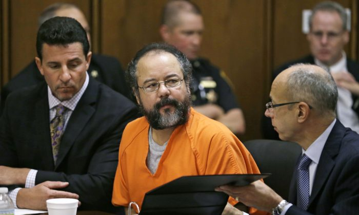 Ariel Castro, center, listens in the courtroom during the sentencing phase Thursday, Aug. 1, 2013, in Cleveland. Defense attorney's Craig Weintraub, left, and Jaye Schlachet sit beside Castro. (AP Photo/Tony Dejak)