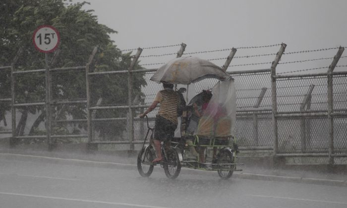 A Filipino man pedals his pedicab during a brief rainfall at Navotas, north of Manila, Philippines, Monday, Aug. 12, 2013. Powerful Typhoon Utor battered the northern Philippines Monday, toppling power lines and dumping heavy rains across mountains, cities, and food-growing plains. The storm killed two men in a landslide and left 45 fishermen missing. (AP Photo/Aaron Favila)