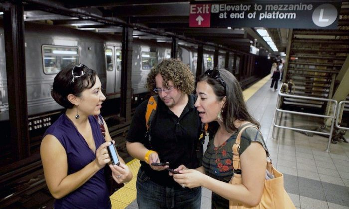 Subway riders test out wireless service at a New York City subway station when it was first rolled out in 2011. (Amal Chen/Epoch Times)