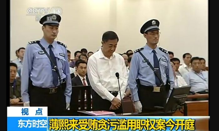 Former Politburo member Bo Xilai stands between two guards at the Jinan Intermediate Court in Shandong Province for the first day of his trial on Aug. 22. Bo gave a combative performance, though the trial elided key details of his activities while in power. (Screenshot/Epoch Times)
